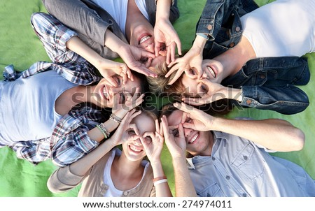 summer holidays, friendship, leisure and teenage concept - group of students or teenagers lying in circle and having fun at campus or park - stock photo