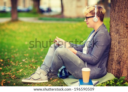 summer holidays, internet and technology concept - teenager with headphones, books, coffee and tablet pc outside - stock photo