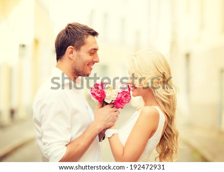 summer holidays, love, relationship and dating concept - couple with bouquet of flowers in the city - stock photo