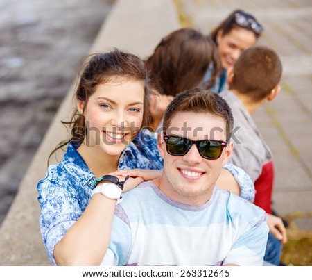 summer holidays, relationships and teenage concept - smiling teenagers having fun outside - stock photo