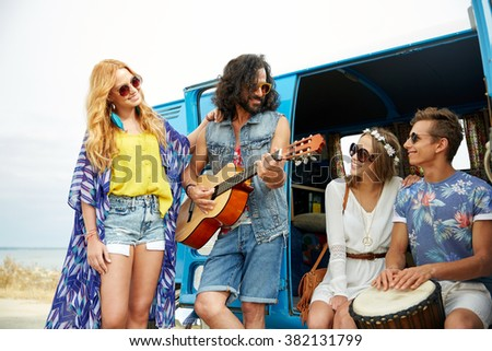summer holidays, road trip, vacation, travel and people concept - happy young hippie friends having fun and playing music over minivan car - stock photo