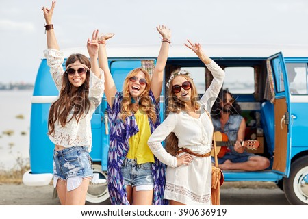 summer holidays, road trip, vacation, travel and people concept - happy young hippie friends having fun and dancing over minivan car - stock photo
