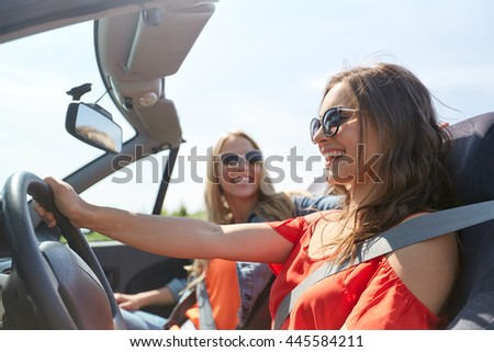 summer holidays, road trip, vacation, travel and people concept - happy young women driving in in cabriolet car and laughing - stock photo