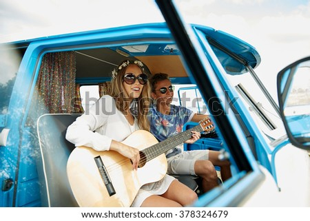 summer holidays, road trip, vacation, travel and people concept - smiling young hippie couple with guitar playing music in minivan car - stock photo
