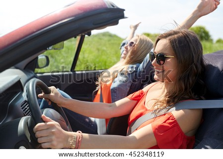 summer holidays, road trip, vacation, travel and people concept - smiling young women driving in in cabriolet car - stock photo