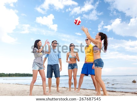 summer holidays, sport, leisure and people concept - group of happy friends playing beach ball - stock photo