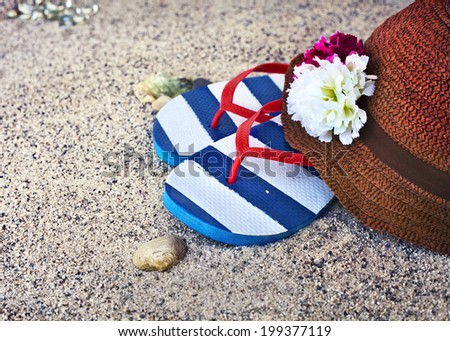 Summer holidays, sunshine on the beach, hat with flowers and flip flops on a tropical beach - stock photo