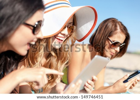 summer holidays, technology and internet concept - girls in bikinis with tablet pc sunbathing on the beach - stock photo