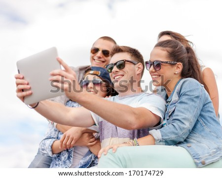 summer holidays, teenage and technology concept - group of smiling teenagers in sunglasses taking selfie with tablet pc - stock photo