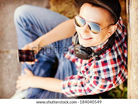 summer holidays, teenage and technology concept - teenager with headphones and smartphone outside - stock photo