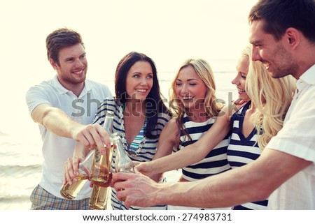 summer, holidays, tourism, drinks and people concept - group of smiling friends clinking bottles of beer or cider on beach - stock photo