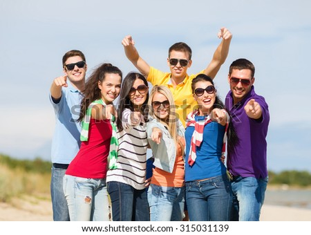 summer holidays, tourism, travel, gesture and people concept - group of happy friends in sunglasses pointing at you on beach - stock photo