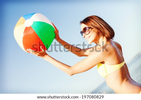 summer holidays, vacation and beach activities concept - girl in bikini playing ball on the beach - stock photo