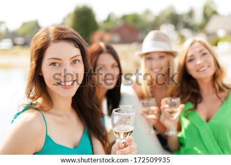 summer holidays, vacation and celebration concept - smiling girls with champagne glasses - stock photo