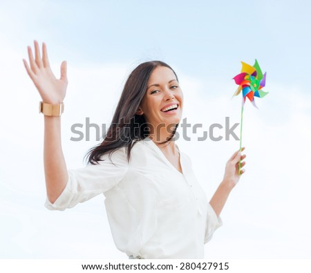 summer holidays, vacation and ecology concept - girl with windmill toy on the beach - stock photo
