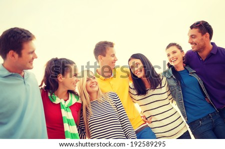 summer, holidays, vacation and happy people concept - group of friends having fun on the beach - stock photo