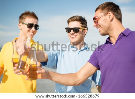 summer, holidays, vacation and happy people concept - group of friends having fun on the beach with bottles of beer or non-alcoholic drinks - stock photo