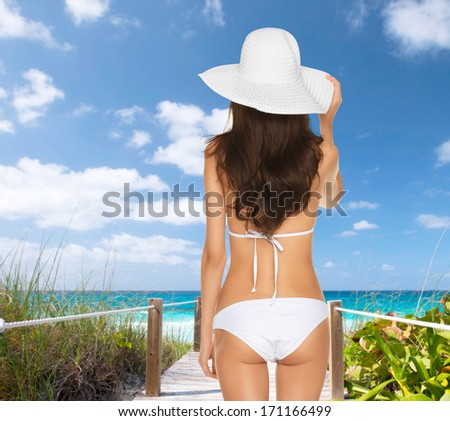 summer holidays, vacation and lingerie concept - back view of beautiful woman in white bikini and hat on a beach - stock photo