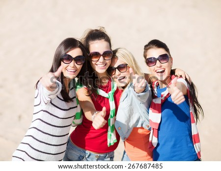summer holidays, vacation and people concept - happy teenage girls in sunglasses or young women showing thumbs up on beach - stock photo
