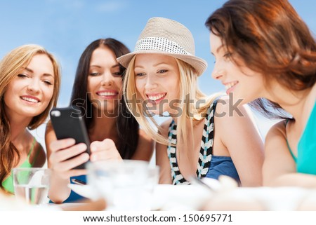 summer holidays, vacation and technology - girls looking at smartphone in cafe on the beach - stock photo