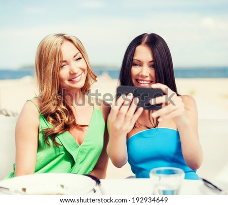 summer holidays, vacation and technology - girls taking photo with smartphone in cafe on the beach