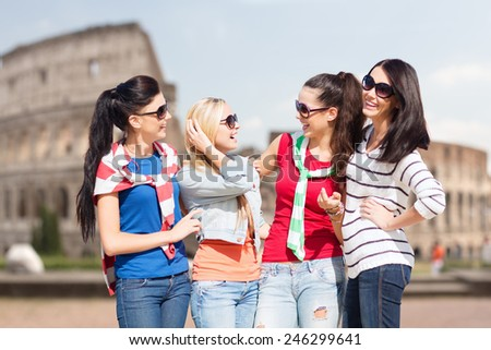 summer, holidays, vacation, friendship and people concept - happy teenage girls or young women in sunglasses talking and laughing over coliseum background - stock photo