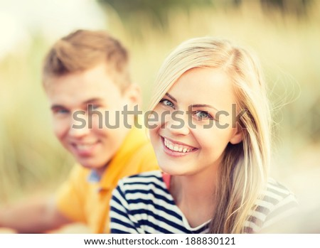 summer, holidays, vacation, happy people and dating concept - couple or friends sitting at the sea side - stock photo