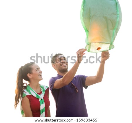 summer, holidays, vacation, happy people concept - couple with chinese sky lanterns on the beach - stock photo