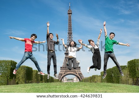 summer, holidays, vacation, happy people concept - group of friends jumping on the park near Eiffel tower in Paris, France - stock photo