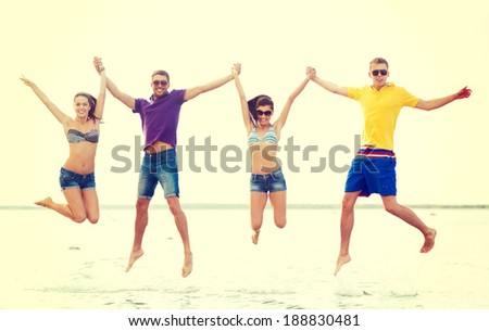 summer, holidays, vacation, happy people concept - group of friends or couples jumping on the beach - stock photo