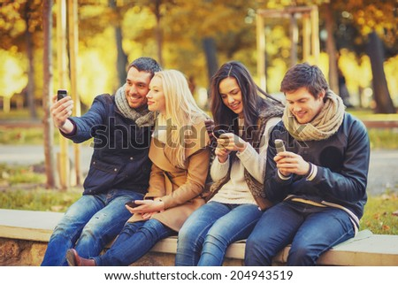 summer, holidays, vacation, happy people concept - group of friends or couples with smartphone having fun in autumn park