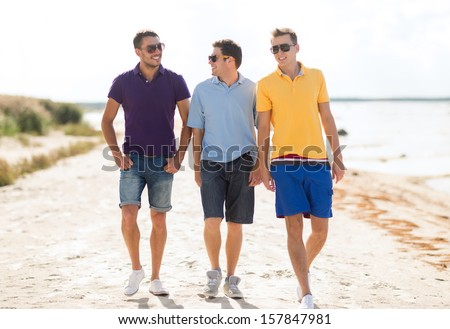 summer, holidays, vacation, happy people concept - group of friends walking on the beach - stock photo