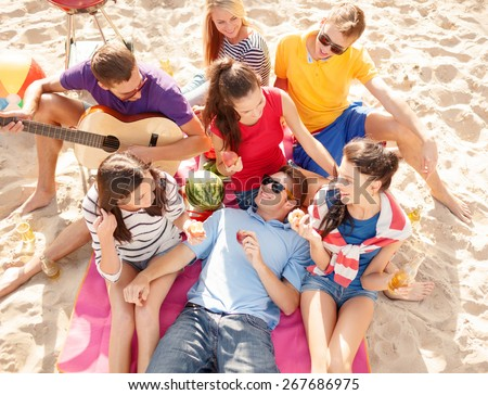 summer holidays, vacation, music, happy people concept - group of happy friends having picnic and playing guitar on beach - stock photo