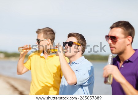 summer holidays, vacation, people and bachelor party concept - group of happy male friends having fun and drinking beer on beach - stock photo