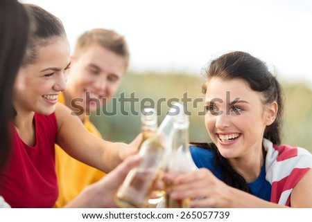 summer holidays, vacation, people and party concept - group of happy friends having fun and drinking beer on beach - stock photo