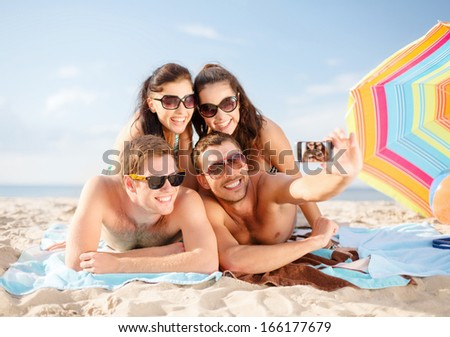 summer, holidays, vacation, technology and happiness concept - group of smiling people in sunglasses taking selfie with smartphone on beach - stock photo