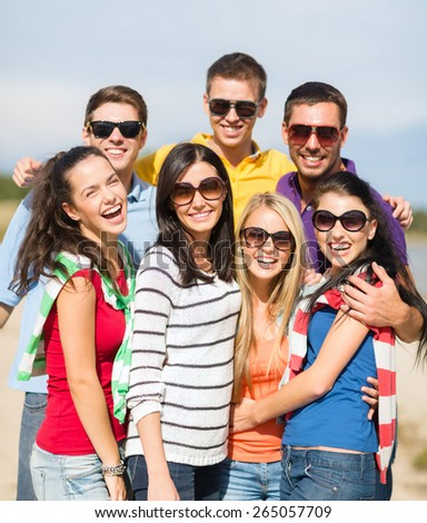 summer holidays, vacation, tourism, travel and people concept - group of happy friends having fun and hugging on beach - stock photo