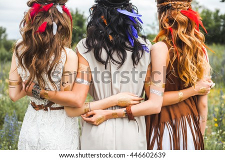 Summer holidays, vacation, travel and people concept - three beautiful hippie girl, photographed from behind, hairstyles, feathers, white dresses, flash tattoo, accessories, Bohemian, Bo-ho Style - stock photo