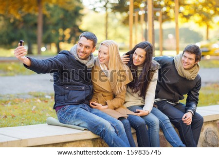 summer, holidays, vacation, travel, tourism concept - group of friends or couples having fun with smartphone photo camera in autumn park