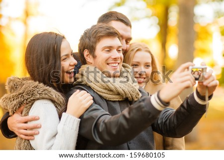 summer, holidays, vacation, travel, tourism, happy people concept - group of friends or couples having fun with photo camera in autumn park - stock photo
