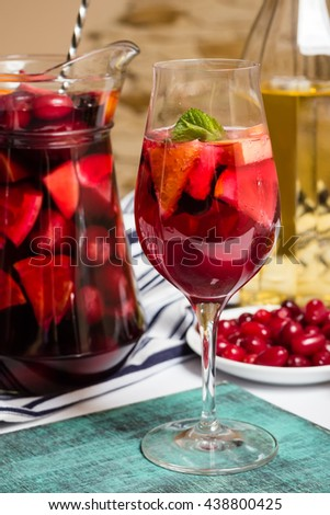 Summer home wine with fruits, sangria cocktail, in glass and jar, fresh dogwood berries plate, bright blue background, food photo - stock photo