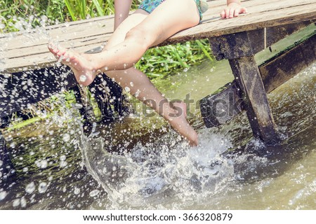 Summer hot day. The girl on the bridge, feet on water podymat splashes. - stock photo