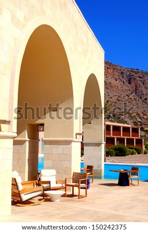 Summer hotel terrace with pool, outdoor wood chairs and table in a luxury resort(Crete, Greece) - stock photo