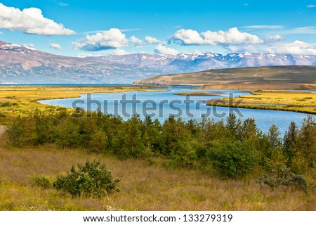 Summer Iceland Landscape with River, Mountains and Bright Blue Sky - stock photo