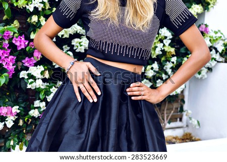 Summer image of pretty woman wearing stylish summer black clothes, trendy jewelry, posing in front of flowers, bright sunny colors. - stock photo