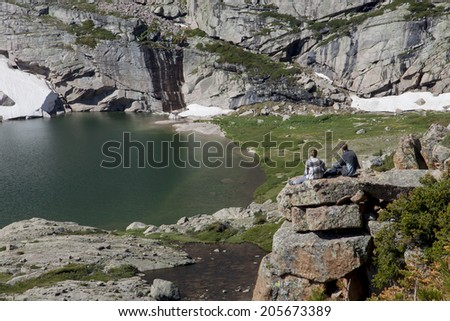 Summer in the Colorado Rockies - Hikers rest on a ledge above the Chasm Lake trail near Longs Peak. - stock photo