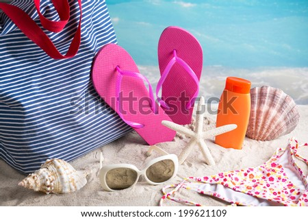Summer items - closeup of summer beach bag with summer accessories - stock photo