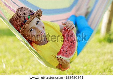 Summer joy - lovely girl eating fresh watermelon in colorful hammock - stock photo