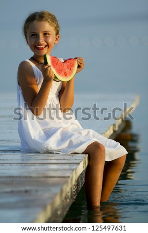 Summer joy, lovely girl eating fresh watermelon on the beach - stock photo