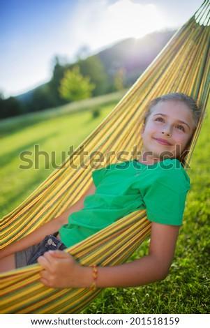 Summer joy  - lovely girl in hammock resting in the garden - stock photo